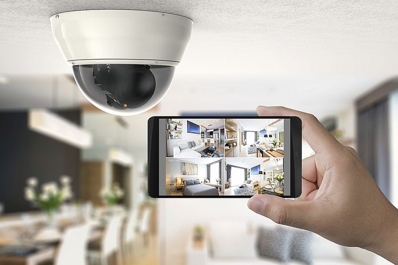 hand holding mobile phone that is connected with a security camera