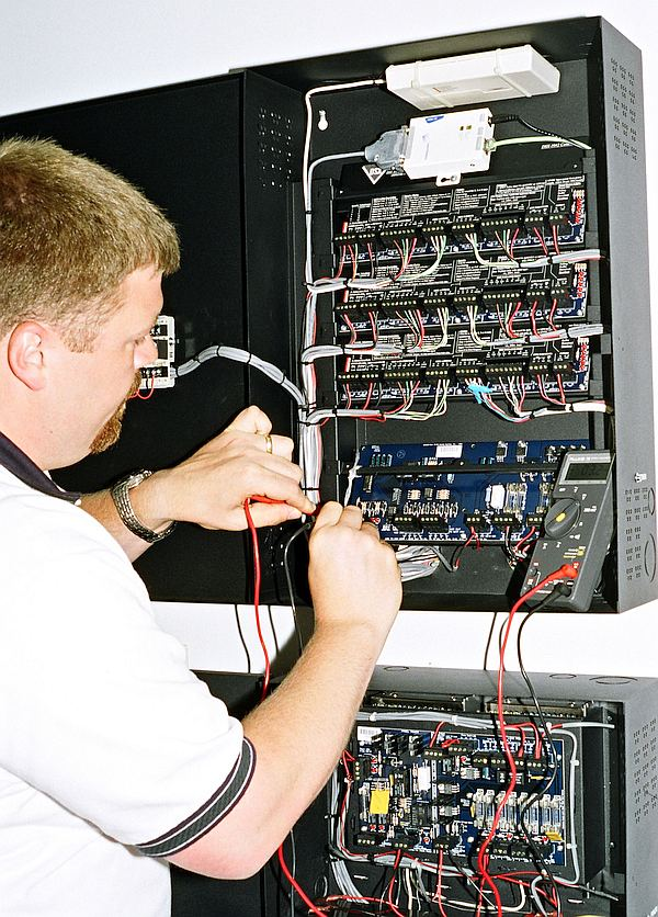 DSI Security Technician working on the business security system.